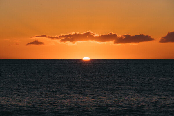 Image of the sun setting at sea. Is the Green Flash Real?