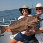 "Grouper Fishing - Capt. Kathy Brown of Miss Judy Charters and Steve Howell, also known as Capt. ""Triple Trouble,"" are holding up his just caught scamp grouper. This fish hit Howell's live bait offering, then it ran for cover under a ledge, and it took about 20 minutes to get it out. A picture in this case is worth about 25 pounds of prime grouper fillets. Photo by Capt. Judy Helmey"