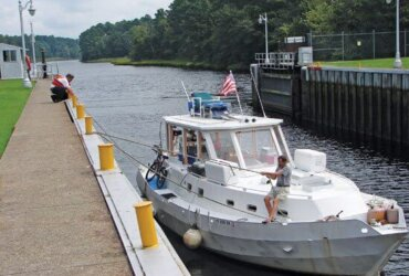 Arnold Parkinson at the bow and Robert Peek secure Pisces for the lock-through to the Great Dismal Swamp. Photo by Kathy Bohanan Enzerink