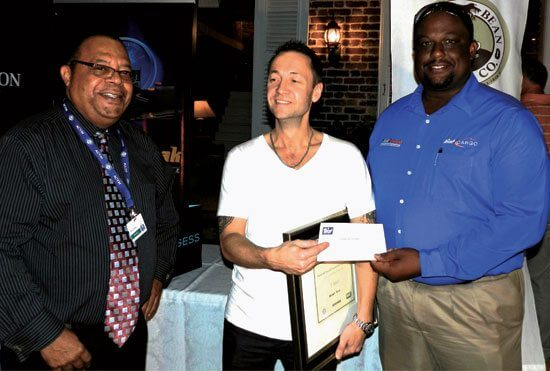 Chef Stuart Ince of M/Y Arianna receiving one of his prizes –  two airline tickets presented by Wilbur Edwards (left) and Troy Bailey of Liat Quikpak  'The Caribbean Airline'. Photos Jan Robinson