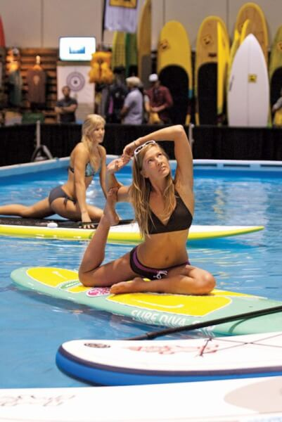 Evey Hammond (front) and Harmony Dawn of Urban Ocean - http://urbanoceansup.com/ in fitness specific swim ware by Prana, demonstrate SUP yoga at Surf Expo in Orlando, Fla. Photo By Glenn Hayes