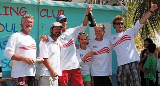 Skipper Frits Bus hoists the champagne as Team Island Water World celebrate their win in Spinnaker Class. Photo by OceanMedia