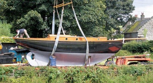 The slings on this wooden boat have been placed beneath the ballast keel, avoiding the deadwood and stem, this is correct. Spreader bars prevent the hull from being nipped.