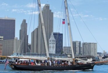 The 1995-built replica of the original America heads to the Louis Vuitton Challenger Cup Finals on San Francisco Bay. The city's landmark Ferry Terminal Building is in the background.