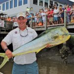 Charles Ragsdale shows off his 34.7-pound mahi to the crowd at Edisto Marina. Photo By Jeff Dennis