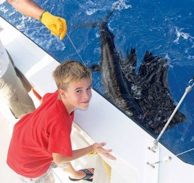 "Captain Gary Clifford says Brennan Adam (8) was the youngest angler to catch a sailfish on his boat ""and he wound it in all by himself."""