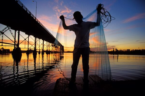 A fisherman inspects his cast net under the bridge in Lake Charles, LA. Photo by Wesley Hitt
