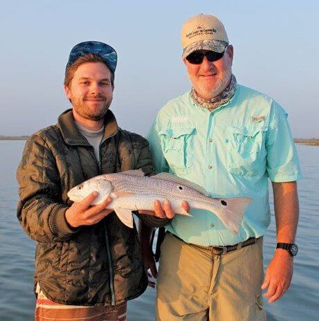 Captain Johan Coombs displays Dave Lear's redfish. Photo By Jeff Dennis