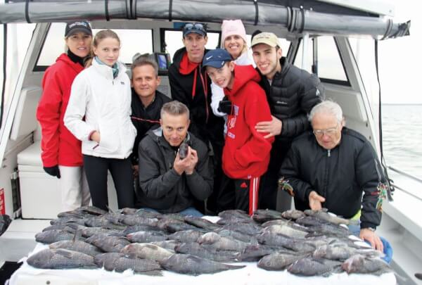 Standing up row from left to right: Susan Stahl, Dagny Stahl, Herb Stahl, Thomas R. James, Audra James (pink cap), William James, (blue cap, red jacket) and Thomas James (tan cap) Front row kneeing: Ken James (holding fish) and Thomas James. Photo by Capt. Judy Helmey