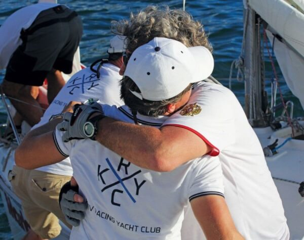 Rodion Luka receives a congratulatory hug from one of the Russian crew. Photo: Gary Brown/OceanMedia