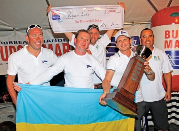 Winning skipper Rodion Luka accepts the winner's trophy from Chris Marshall (far right) of Budget Marine. Photo: Bob Grieser