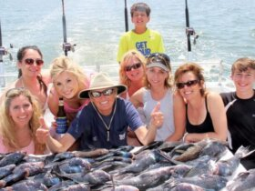 Left to right front: Kara Shannon, Jessica Leterra, Laura Pruitt (holding Miss Judy koozie), Captain Judy, Suzanne Saeed (with sunglasses), Tina Stone (sunglasses on cap), Melody McElwee, Ryan McElwee. Standing in back: Aiden Saeed. Photo by Captain Kathy Brown