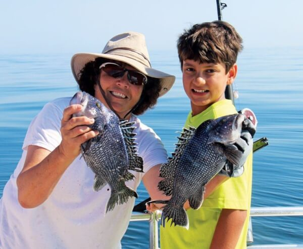 Captain Kathy Brown holding Aiden Saeed's double header catch of black sea bass.