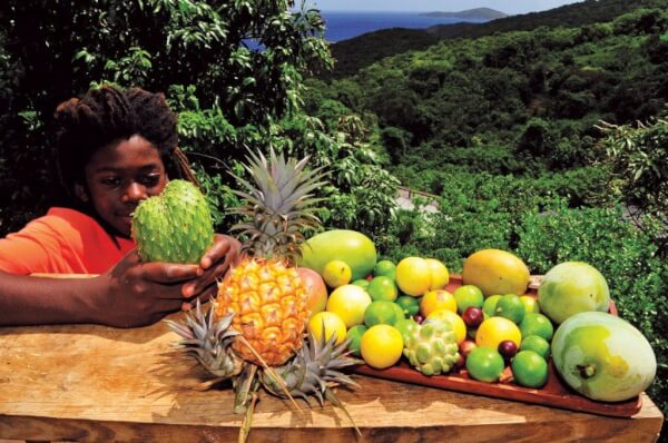 Lukata Samuel of St. Thomas holds a soursop. Other fruits include pineapple, mangoes, guavas, limes and West Indian cherries. Photography by Dean Barnes