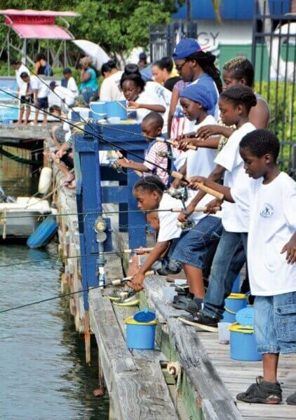A crowd of kids and their parents fish on the docks of IGY's American Yacht Harbor