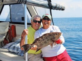 Travis Durham and Captain Kathy Brown look like good looking fishing team to me. Captain Kathy Brown is holding up Travis's just caught scamp grouper! Photo by Captain Judy Helmey