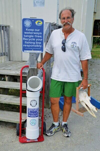 """Keith Rittmaster poses beside his mobile monofilament recycling bin. He's holding """"Lionel"""" the 6- month old bottlenose dolphin that has fused fishing line in and around its jaws. Photo by Helen Aitken"""