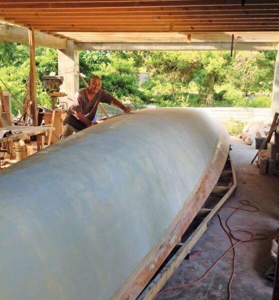 Fairing the hull with a longboard. Photos by SteveBrett