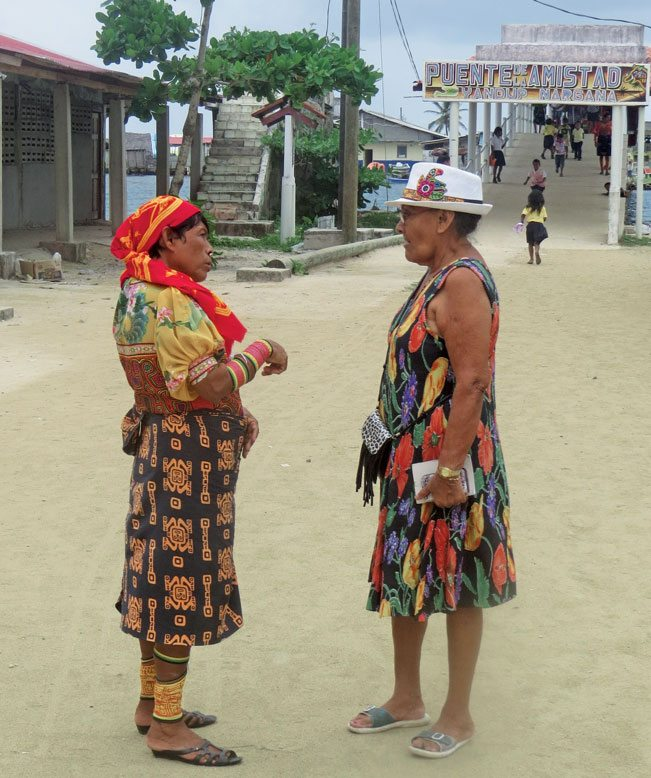 Two Guna ladies in Nargana, both colorfully dressed; one traditionally and one for the city. Photo by Barbara Hart