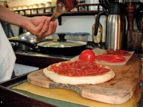 Cooking at Sea: Pizza being made on a two-burner stove by Connie McBride. Connie McBride