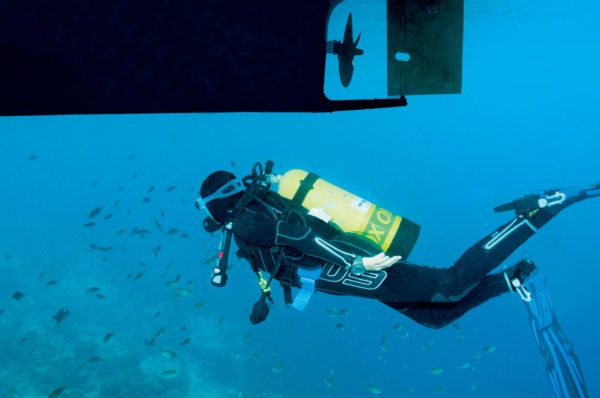 Why Diving on Scuba is Better Than Snorkeling: Surrounded by fish, Barbara swims alongside the keel of Tusen Takk II. Photo by Charles (Chuck) Shipley