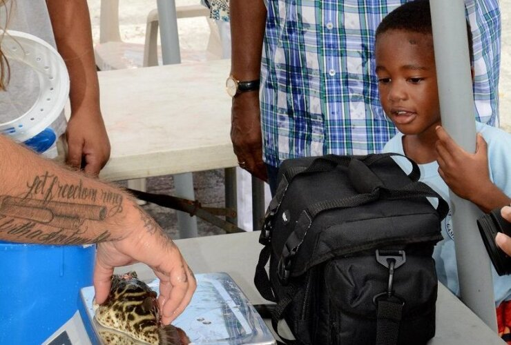 Four-year-old Kadmiel Warrell weighs in is catch at last year's Virgin Islands Game Fishing Club's Kid's Fishing Tournament, with the help of adult, WSTA radio personality, Addie Ottley. Credit: Dean Barnes