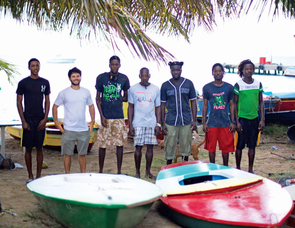 A group of kids that hope to become instructors and racers stand next to some of their boats in Mayreau. Photo: Jost Van Dyke Preservation Society