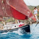 The yacht Buxom with her traditional tan sails and awesome figurehead