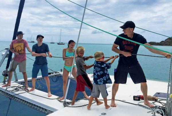 Raising the mainsail with guests and extended family in Antigua (from left): Braden, Findlay and Jorja Armstrong, Paul and Henry Escher and Rick Armstrong. Photo by Lorraine Escher