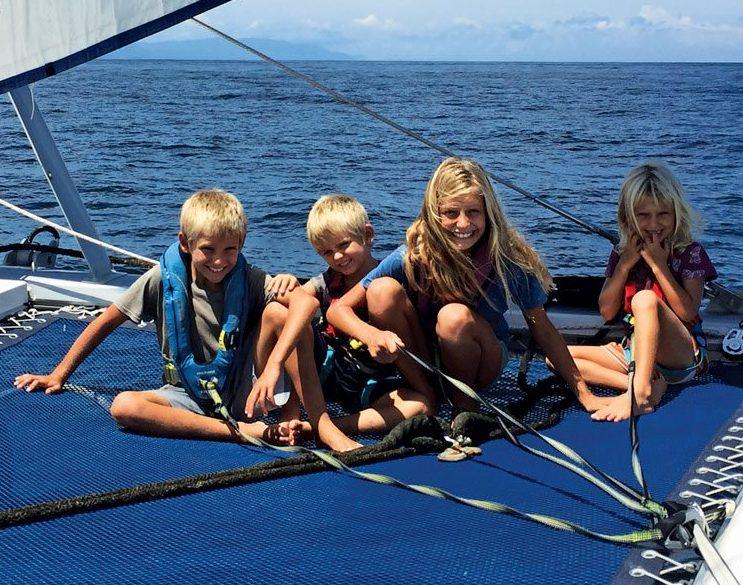 The Escher kids Paul (9), Henry (6), Betty (11), and Karen (6) forgo a trampoline in the back yard for a trampoline on an ocean-going catamaran. Photo by Lorraine Escher