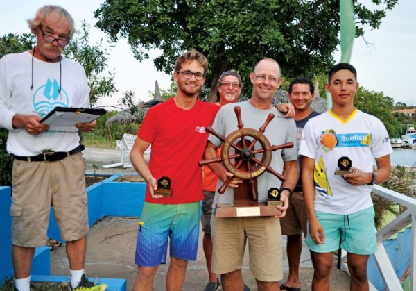 Winners of the Wim van der Gulik Sunfish Races (from left): Tijn van der Gulik, Hans van der Gulik and Darius Berenos, accompanied by the race committee. Photo by Els Kroon
