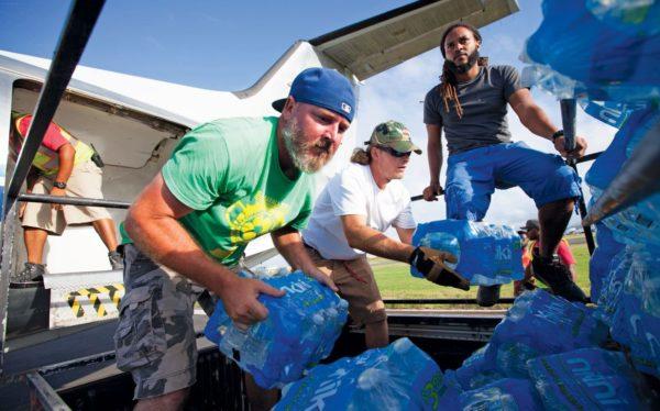 Volunteers unload relief supplies into waiting pickup trucks in Anguilla after Hurricane Irma