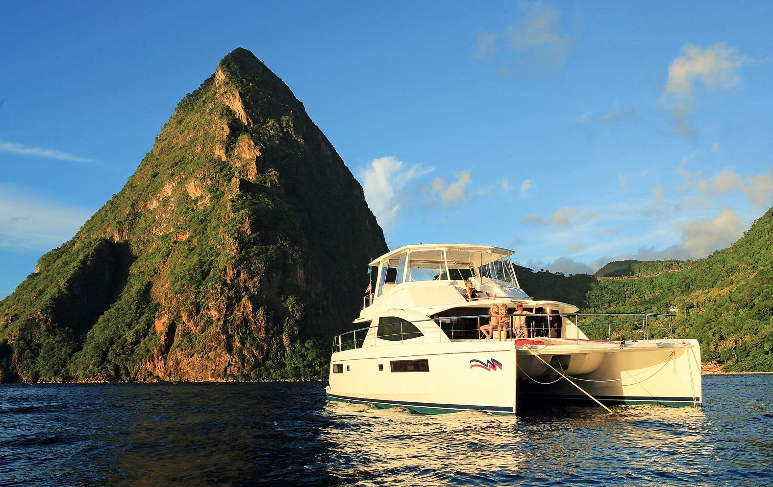 A young family enjoy the space and stability of a power cat at anchor in the shadow of the Pitons, St. Lucia. Photo courtesy of The Moorings