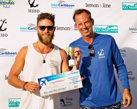 A grin from winner John Sloan (left) as he receives his InterCaribbean Round Trip Ticket to Anywhere