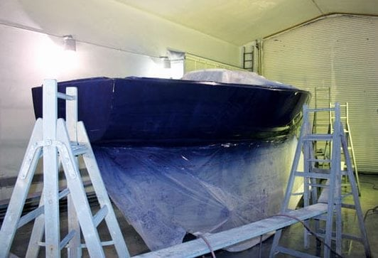 The first coat of topside paint has been sprayed on. Notice the bottom and the deck are covered, but you can see overspray on both surfaces
