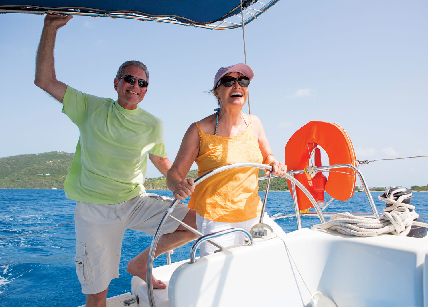 A couple sail their charter boat through the British Virgin Islands. Photo courtesy of the Moorings