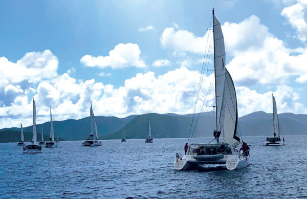 Yachts in Foxy's Cat Fight cross the start line in light winds. Photograph by Susan Zaluski