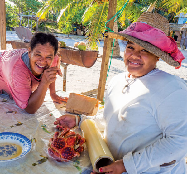 Adrienne and his daughter Faimana wrap up a cooked landcrab to go