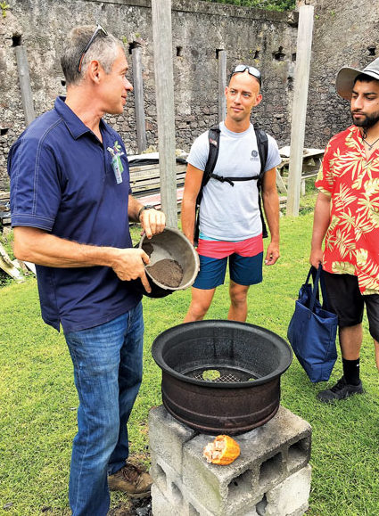 Jonathan Lehrer (left) shows Rian Bareuther of St. Thomas (center) and Arjun Verma from Toronto, Canada, the historic way to dry cocoa beans.