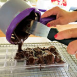 Pouring the tempered chocolate into molds.