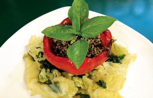 ROASTED BELL PEPPERS STUFFED WITH QUINOA ON SPINACH AND CABBAGE