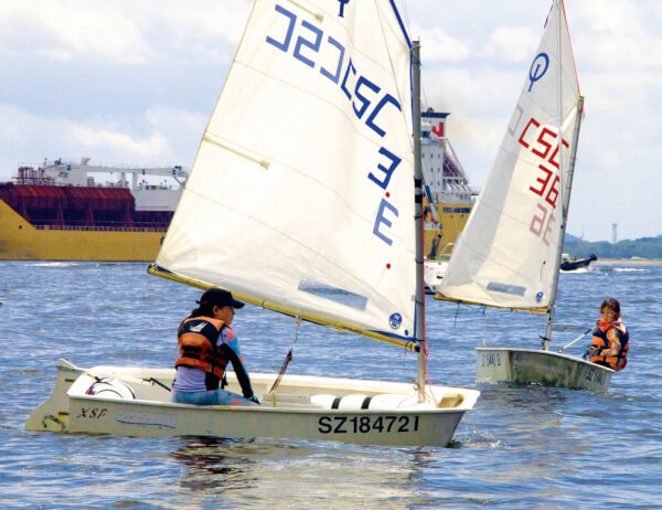 Optimist sailing program - Soku Starboard tacks Charlene (Note freighter on the race course), Opti Singapore CSC
